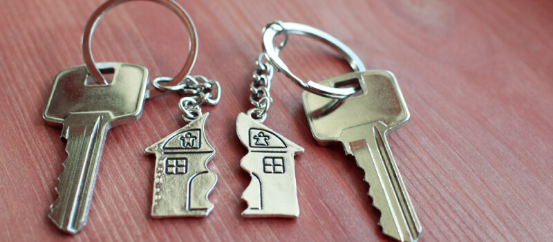two sets of keys with half house keychain on each
